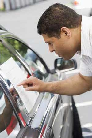 Man reading informational window sticker on vehicle
