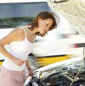 Woman checking oil in car